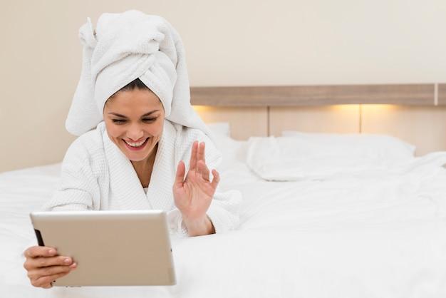 Femme à l'aide d'une tablette dans une chambre d'hôtel