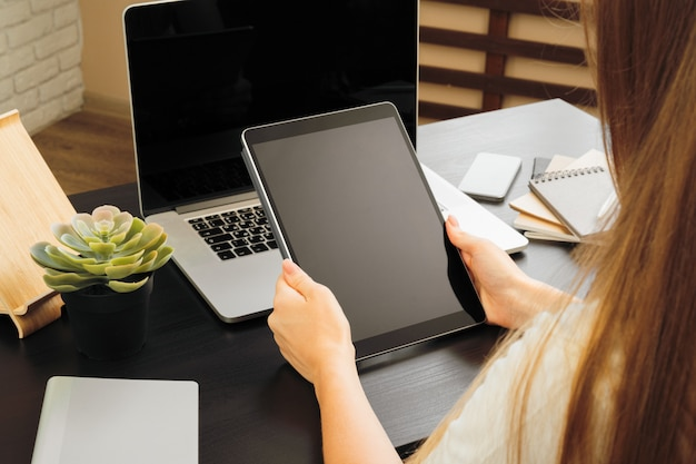 Femme à l'aide d'une tablette numérique, assis à une table dans un bureau