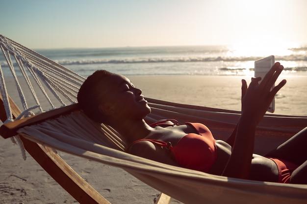 Femme à l'aide de tablette numérique tout en vous relaxant dans un hamac sur la plage