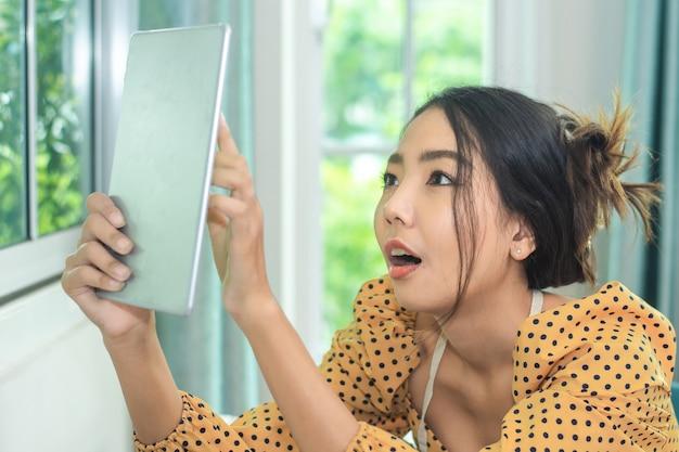 Femme à l'aide d'une tablette pour la boutique de publicité sur la technologie des médias sociaux internet