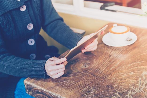 Femme à l'aide de la tablette et la profondeur de champ dans un café avec ton vintage.