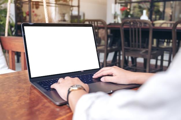 Femme à l'aide et en tapant sur ordinateur portable avec écran blanc vierge sur table en bois