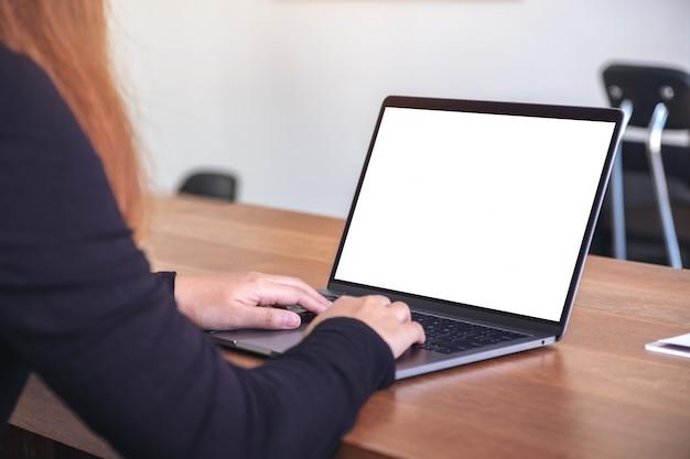 Une femme à l'aide et en tapant sur un ordinateur portable avec un écran de bureau blanc vierge sur une table en bois au bureau
