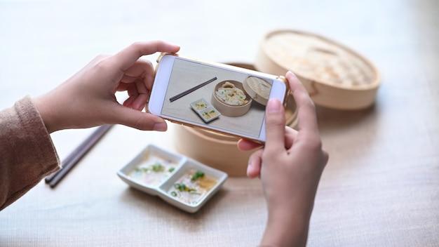 Femme à l'aide de téléphone intelligent prenant des photos de boulettes japonaises originales sur table en bois.
