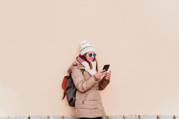 Femme à l'aide de téléphone portable sur le mur jaune. technologie et concept d'hiver