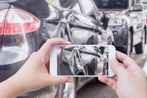 Femme à l'aide de téléphone portable en prenant une photo de l'accident de voiture
