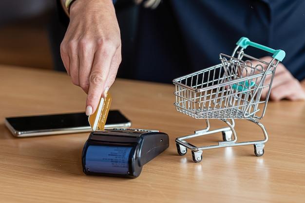 Femme à l'aide de terminal de carte de paiement pour faire des achats en ligne avec carte de crédit, lecteur de carte de crédit, concept de finance