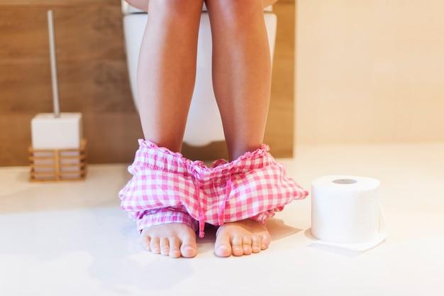 Femme à l'aide de toilettes le matin