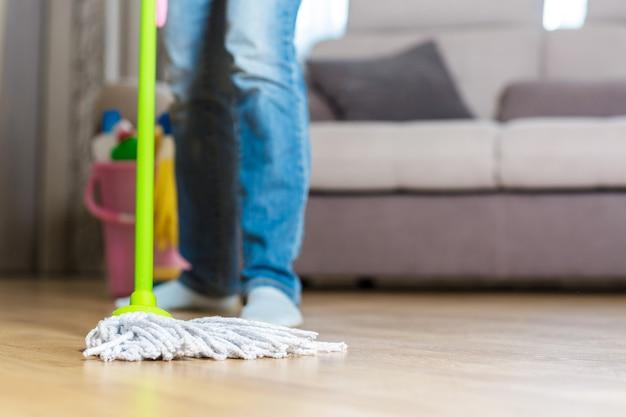 Femme à l'aide d'une vadrouille pour nettoyer le sol