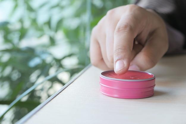 Femme à l'aide de vaseline sur la peau à la maison se bouchent.