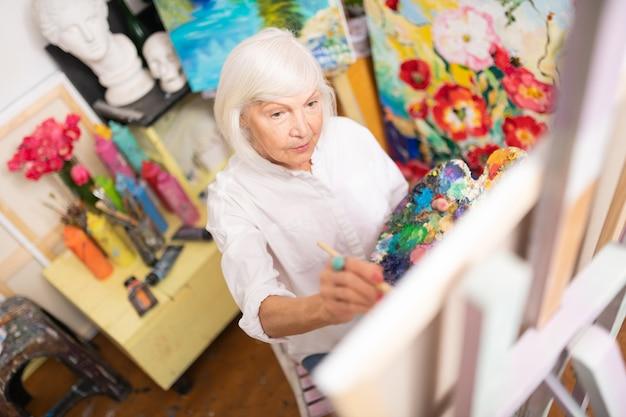 Femme aimant la peinture. femme à la retraite créative aux cheveux blonds aimant la peinture à colorier sa photo