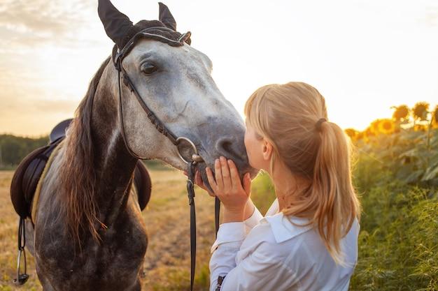 Une femme aime un cheval. amour et amitié pour l'animal, soins. beau champ au coucher du soleil, tournesols. sport équestre, dressage, marche, location et vente, munitions. vacances en plein air, bisous