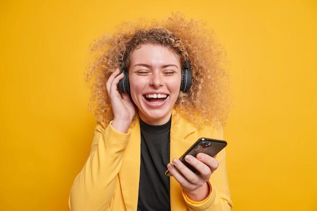 Une femme aime écouter de la musique avec des écouteurs garde les yeux fermés tient un téléphone portable exprime des émotions joyeuses authentiques oublie tous les problèmes a des cheveux bouclés naturels