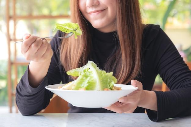 Une femme aime manger une salade césar