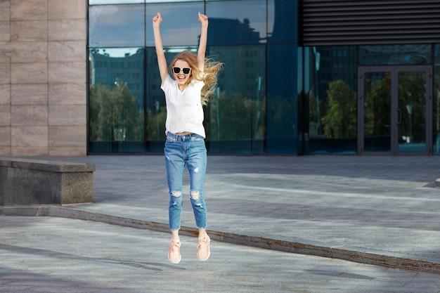 Une femme aime et saute en été à l'extérieur du bâtiment des vacances d'été