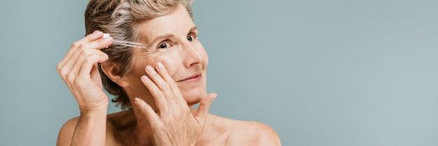 Femme aînée appliquant la crème hydratante sur ses rides d'oeil