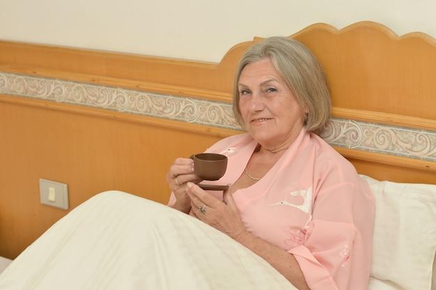 Femme aînée, dans, chambre à coucher, à, tasse café