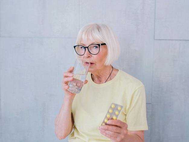 Femme aînée, dans, lunettes, tenue, médecine, pilules, et, verre eau