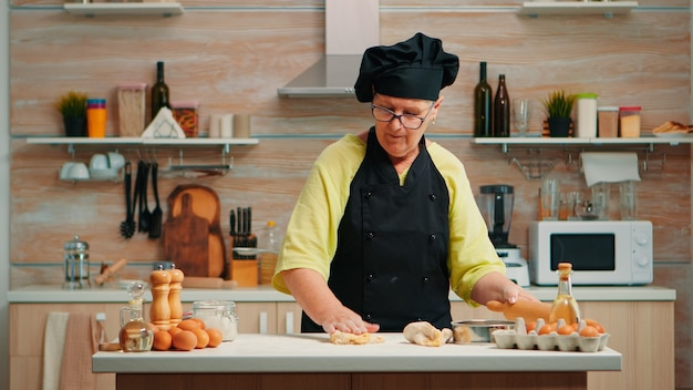 Femme aînée déployant la pâte préparant du pain fait maison. heureux chef âgé avec bonete préparant des ingrédients crus pour la cuisson de pizzas traditionnelles saupoudrées, tamisant la farine sur la table dans la cuisine.