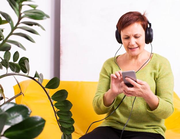 Femme aînée écoutant de la musique et regardant au téléphone