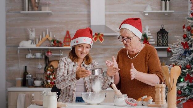 Femme aînée enseignant le petit-fils à qui filtrer l'ingrédient de la farine dans un bol