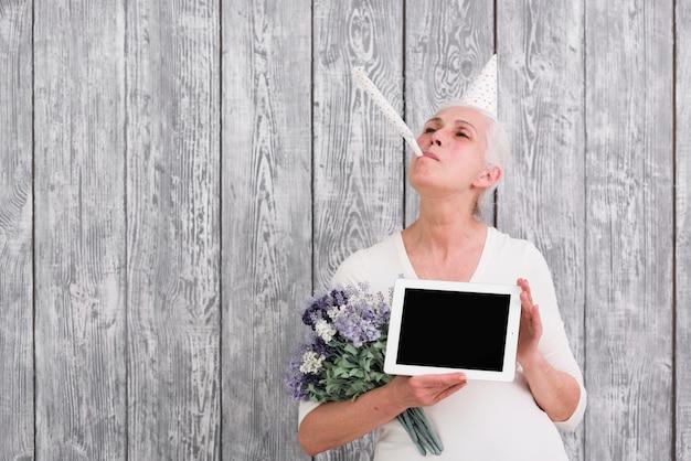 Femme aînée gaie, soufflant dans une corne de fête tenant une tablette numérique et un bouquet de fleurs pourpres à la main
