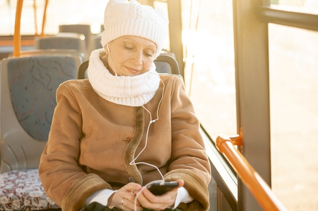 Femme aînée grand angle, dans, bus, écouter musique