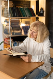 Femme aînée, lecture livre, chez soi