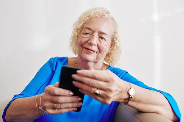 Femme aînée, lecture, message texte