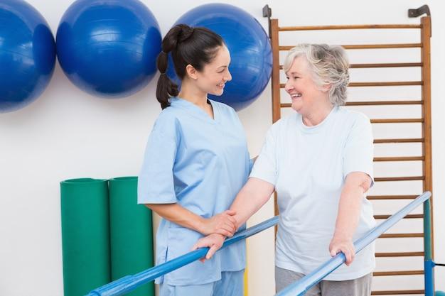 Femme aînée, marche, à, barres parallèles, à, thérapeute