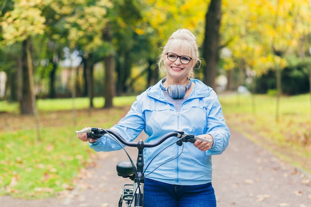 Femme aînée, marche, dans parc, à, vélo