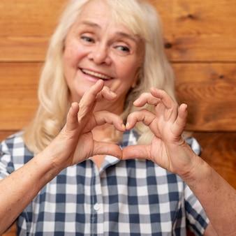 Femme aînée montrant la forme de coeur de la main
