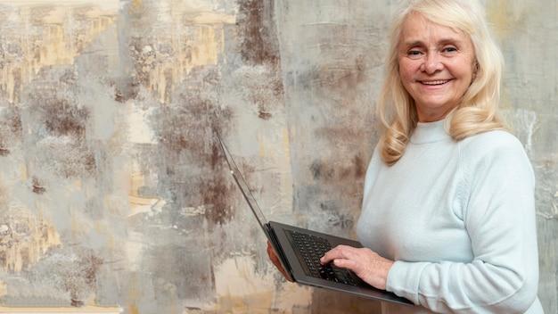 Femme aînée avec un ordinateur portable à la fenêtre gelée