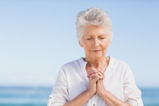 Femme aînée, prier, plage