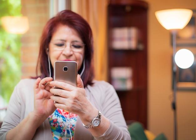 Femme aînée, utilisation, nouvelle technologie, regarder vidéos, sur, elle, smartphone