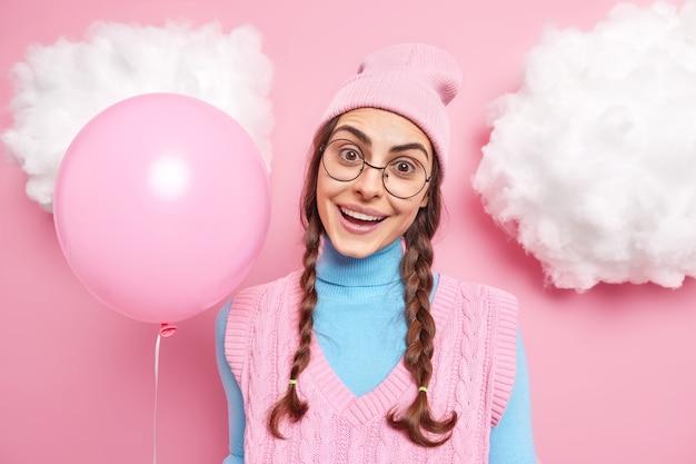 La femme a l'air joyeusement a deux tresses sourit porte agréablement des vêtements décontractés tient un ballon gonflé vient à la fête pour féliciter un ami avec son anniversaire