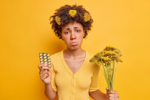 La femme a l'air tristement pus les lèvres tient des pilules pour traiter l'allergie a des symptômes désagréables tient des fleurs sauvages cueillies dans un champ isolé sur jaune