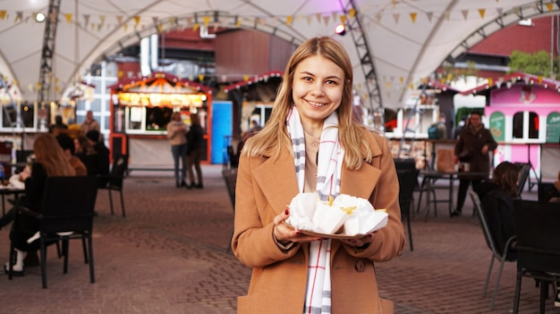 Femme à l'aire de restauration avec food trucks la blonde a acheté de la nourriture de rue