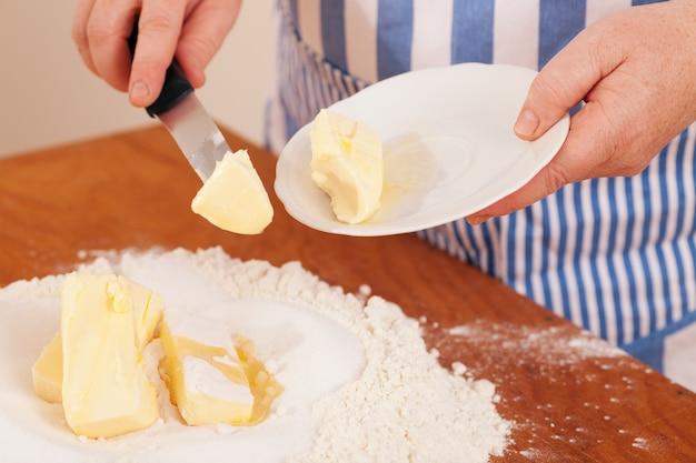 Femme ajoutant du beurre à un mélange