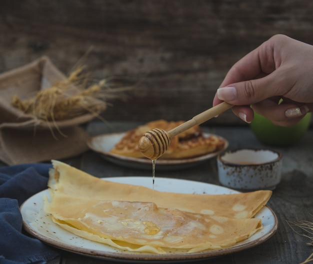 Femme ajoutant du miel aux crêpes.