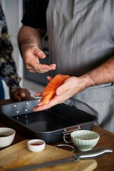 Femme ajoutant des épices et des herbes au saumon cru