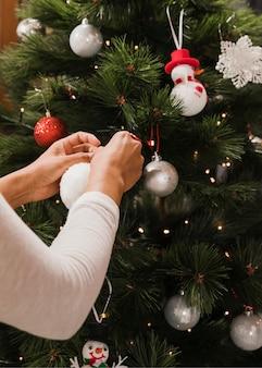Femme ajoutant des jouets à l'arbre de noël