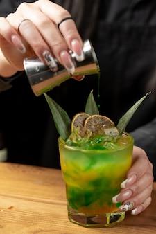 Femme, ajouter, eau, dans, cocktail orange citron vert