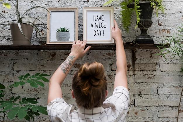 Femme ajustement avoir un beau cadre photo sur une étagère