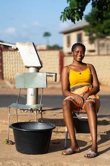 Femme allant chercher de l'eau à l'extérieur