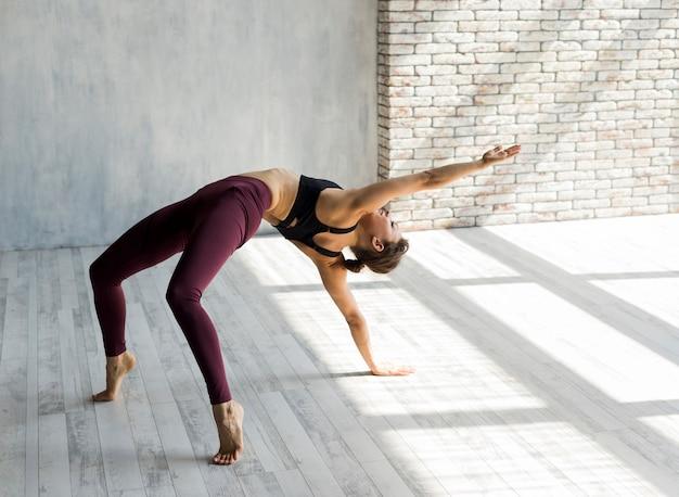 Femme allongeant le bras dans une pose de pont