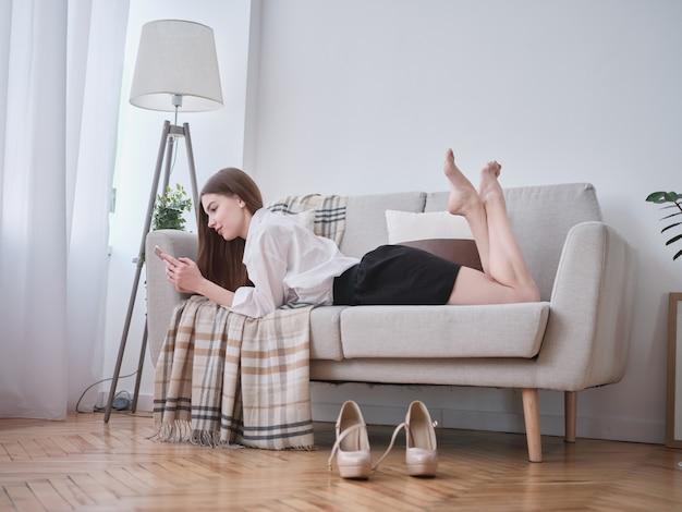 Femme allongée sur le canapé dans le salon avec smartphone