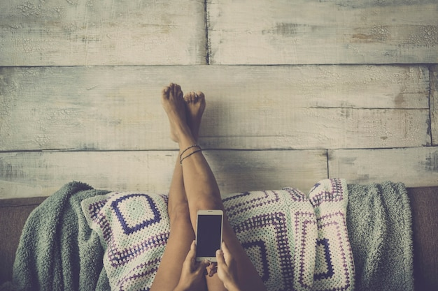 Femme allongée sur le canapé avec les jambes reposant sur le mur détendue en regardant le téléphone - concept de fille seule à la maison avec la technologie - style de couleur gris vintage