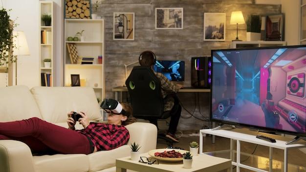 Femme allongée sur un canapé jouant à des jeux vidéo à l'aide d'un casque vr dans le salon. petit ami jouant sur ordinateur.