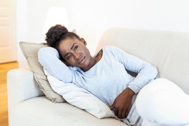Femme Allongée Sur Le Canapé à La Recherche De Malades Dans Le Salon Photo Premium